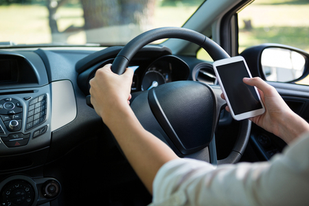 Mid-section of woman using mobile phone while driving a car Stock Photo