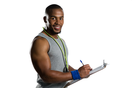 Portrait of smiling male rugby coach writing on clipboard while standing against white background