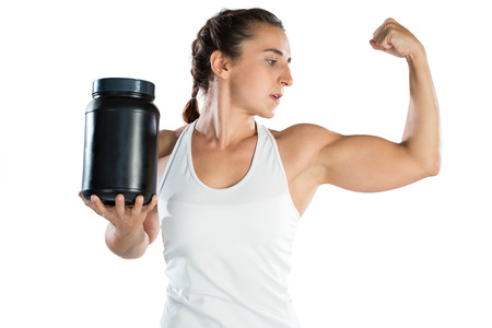 Female athlete flexing muscles while holding supplement jar against white background