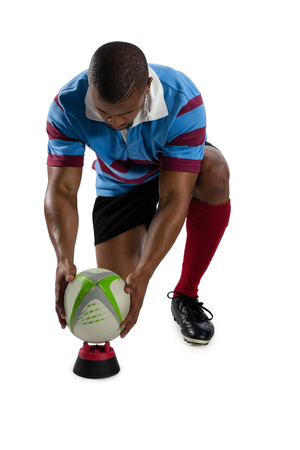 Full length of male rugby player keeping ball on tee while kneeling against white background