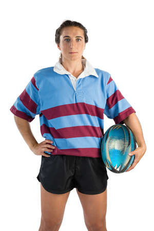 Portrait of confident female athlete with hand on hip holding rugby ball against white background