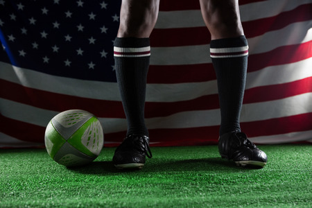 low section: Low section of rugby player standing on field against American flag Stock Photo