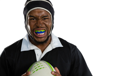 Portrait of male rugby player wearing mouthguard white holding rugby ball against white background
