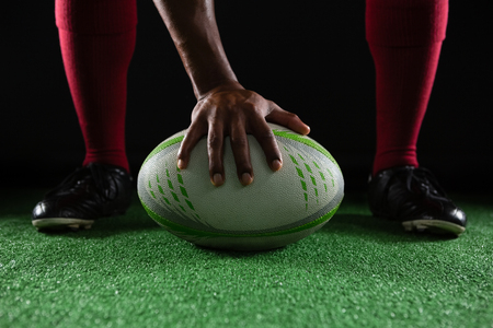 low section: Low section of sportsperson on rugby ball against black background Stock Photo