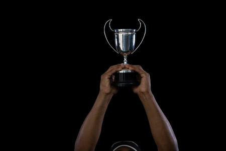Cropped hand on sportsperson holding trophy against black background Stock Photo