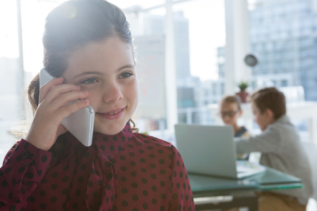 Girl as business executive talking on mobile phone in office