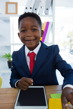 Portrait of boy as business executive smiling while sitting in office Stock Photo