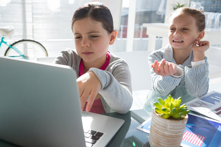 Kids as business executives discussing over laptop in office