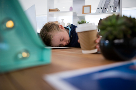 Boy as business executive sleeping while holding coffee cup in office