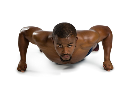 Portrait of sportsman practicing push ups against white background