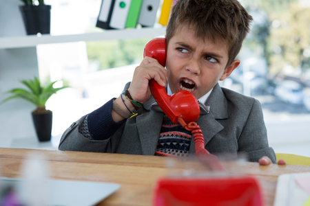Boy as business executive talking on phone in office