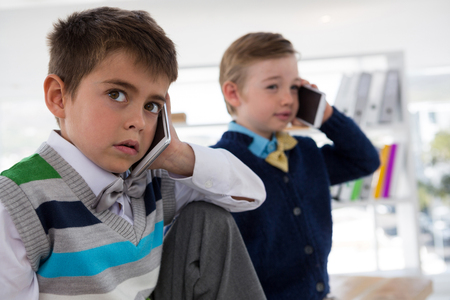 Kids as business executives talking on mobile phone in office