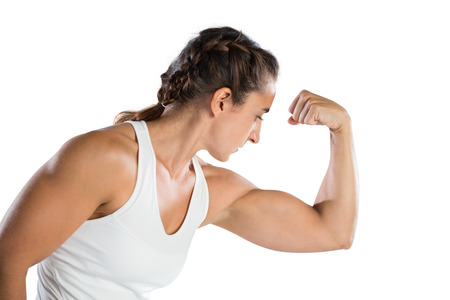 Female athlete flexing muscles against white background Stock Photo