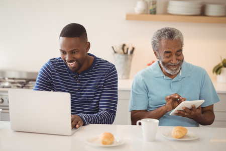 Smiling father and son using laptop and digital tablet in kitchen at home