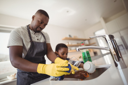 Father and son cleaning utensils in kitchen at home
