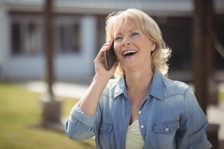 Smiling senior woman talking on mobile phone outside his house on a sunny day