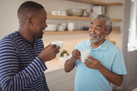 Smiling father and son interacting while having cup of coffee at home Stockfoto