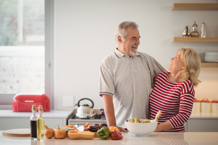 Smiling senior couple embracing each other in kitchen at home