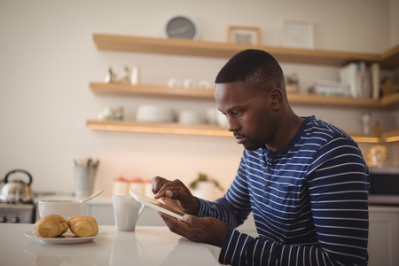 Man using a digital tablet in kitchen at home Stock Photo