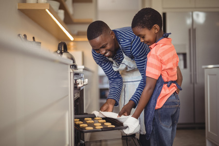 Smiling father taking tray of fresh cookies out of oven with son in kitchen at home Stock Photo