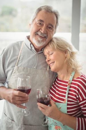 Smiling senior couple holding wine glass in kitchen at home