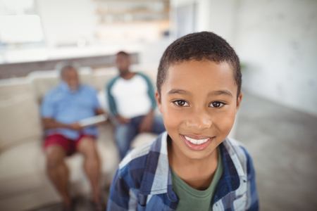 Portrait of smiling boy standing in living room at home