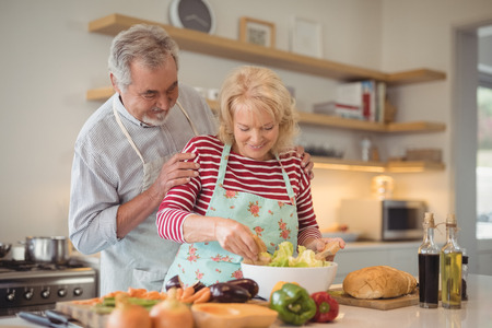 Smiling senior couple mixing vegetables salad in bowl at kitchen