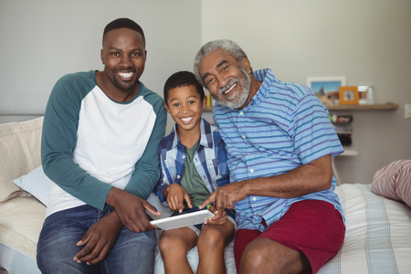 Portrait of happy multi-generation family using digital tablet on bed in bedroom