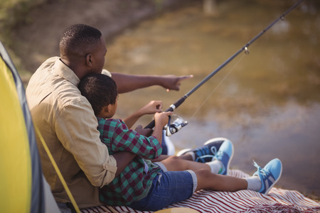 Rear view of father and son fishing together in park