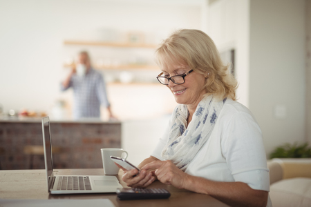 Senior woman using mobile phone at home