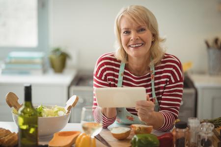 Senior woman using digital tablet in kitchen