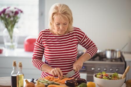 Senior woman chopping vegetables at home