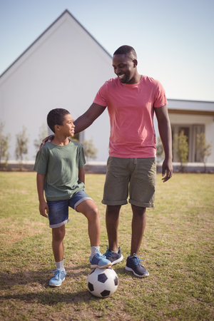 Smiling father and son standing in garden with football on a sunny day Stock Photo