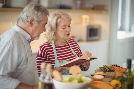 キッチンで食事を準備しながらレシピ本を読んでシニア カップル 写真素材