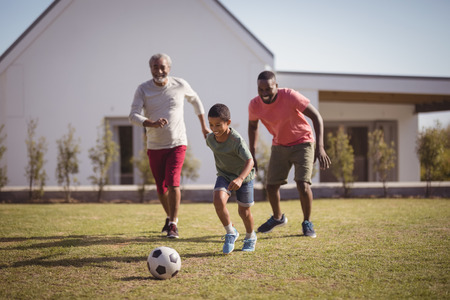 Boy playing football with his father and grandson in garden
