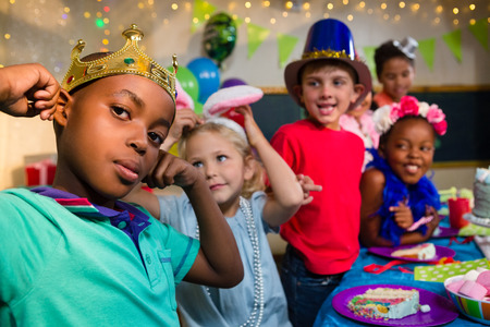 Playful kids at table during birthday Stock Photo