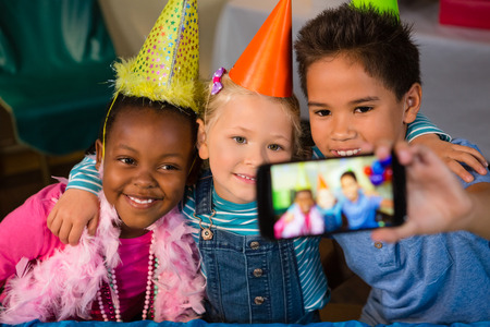 Kids talking selfie through smartphone during birthday party