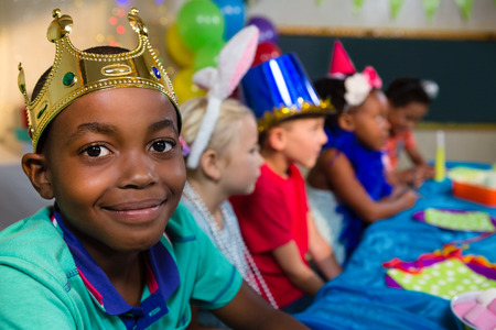 Portrait of smiling boy wearing crown with friends in background during party