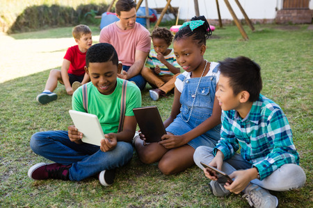 Children using digital tablet while sitting with man on field at park