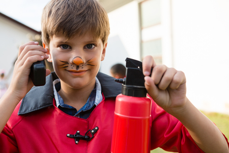 Portrait of boy with face paint using walkie talkie while holding fire extinguisher during birthday party Stock Photo