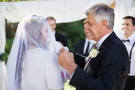 Happy father removing veil of his daughter during wedding 스톡 콘텐츠