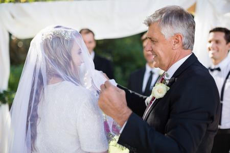 Gelukkige vader verwijderen van sluier van zijn dochter tijdens de bruiloft