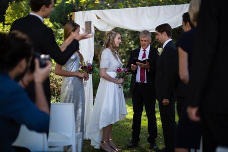Minister Giving Speech To Bride And Groom During Wedding Photo