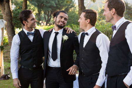 Happy groom and groomsmen having fun in park