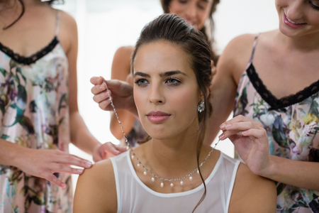 nightwear: Bridesmaid assisting bride in getting ready at home