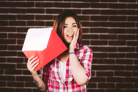 Surprise woman holding envelope against brick wall