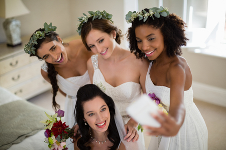 Smiling bride and bridesmaid taking selfie at home Stock Photo