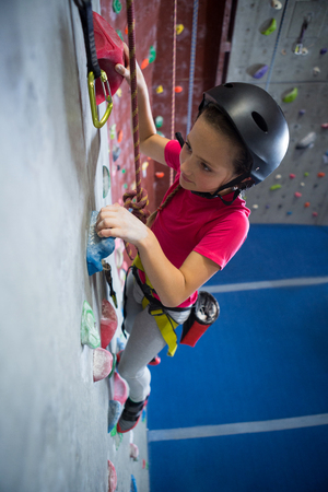 Determined teenage girl practicing rock climbing in fitness studio Stock Photo