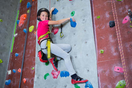 Portrait of confident teenage girl practicing rock climbing in fitness studio