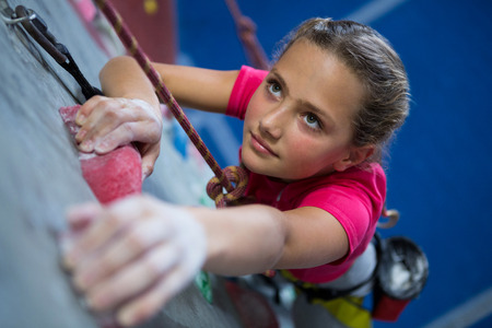 Determined teenage girl practicing rock climbing in fitness studio 스톡 콘텐츠